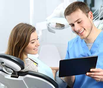 Image of a Dentist showing some reports to patient, Patient is sitting on the dentist chair
